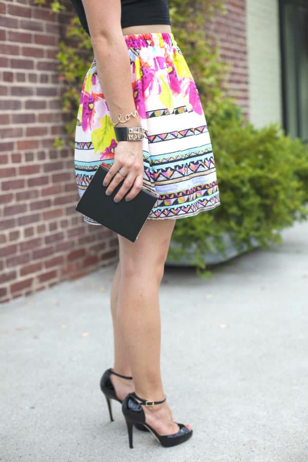 printed skirt and black clutch