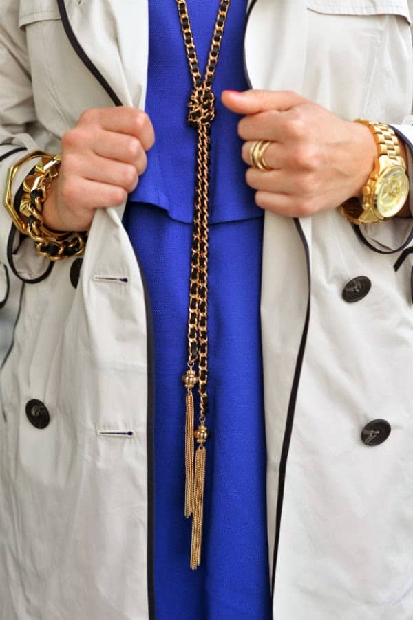 gold tassel necklace with blue dress and trench