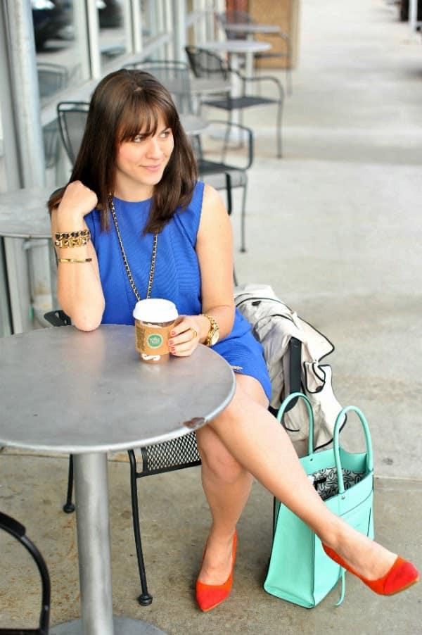 woman sitting having coffee in blue dress