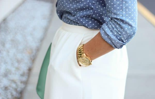 gold watch and white skirt