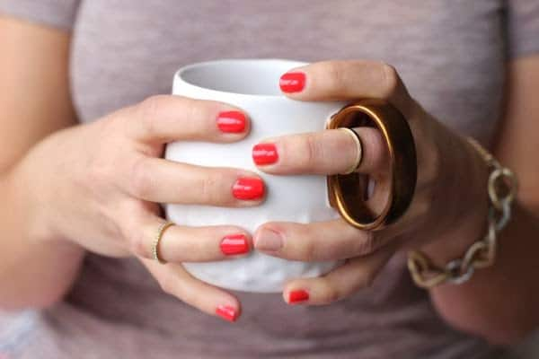 red nails holding coffee