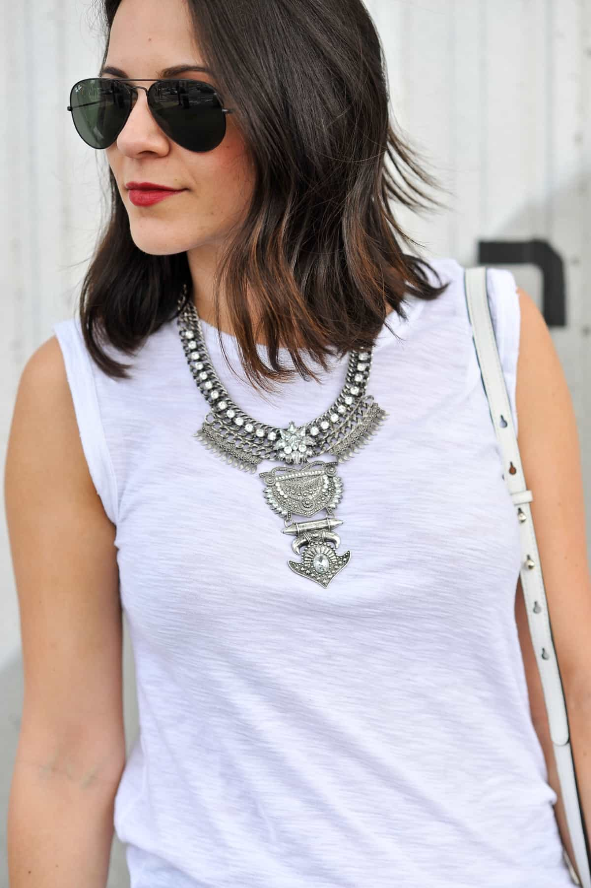 White muscle tee with a statement necklace