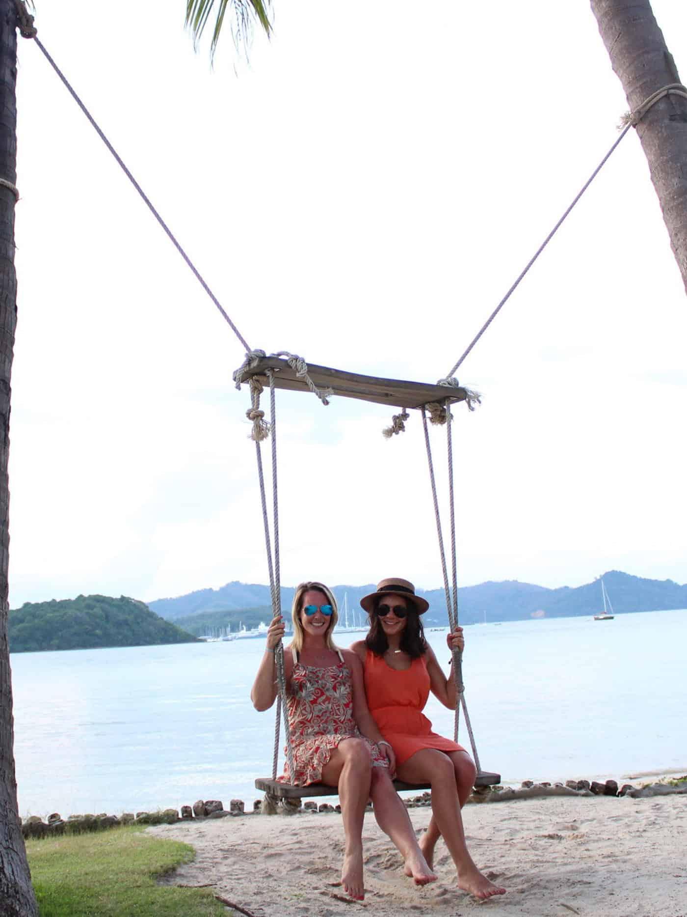 Friends sitting on a swing in Phuket