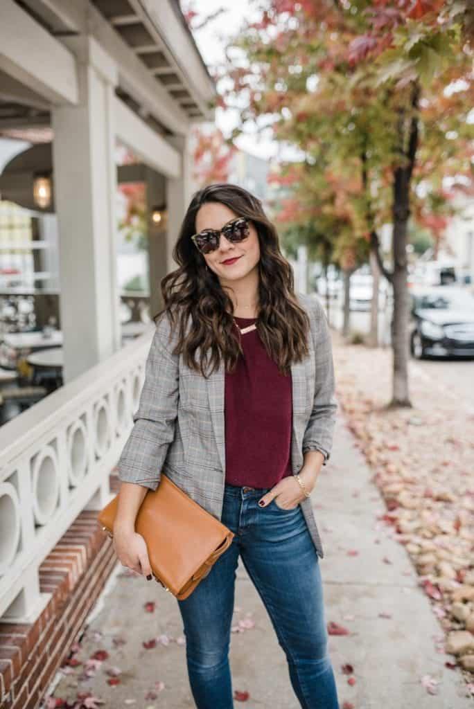 a girl in a blazer with a tan bag