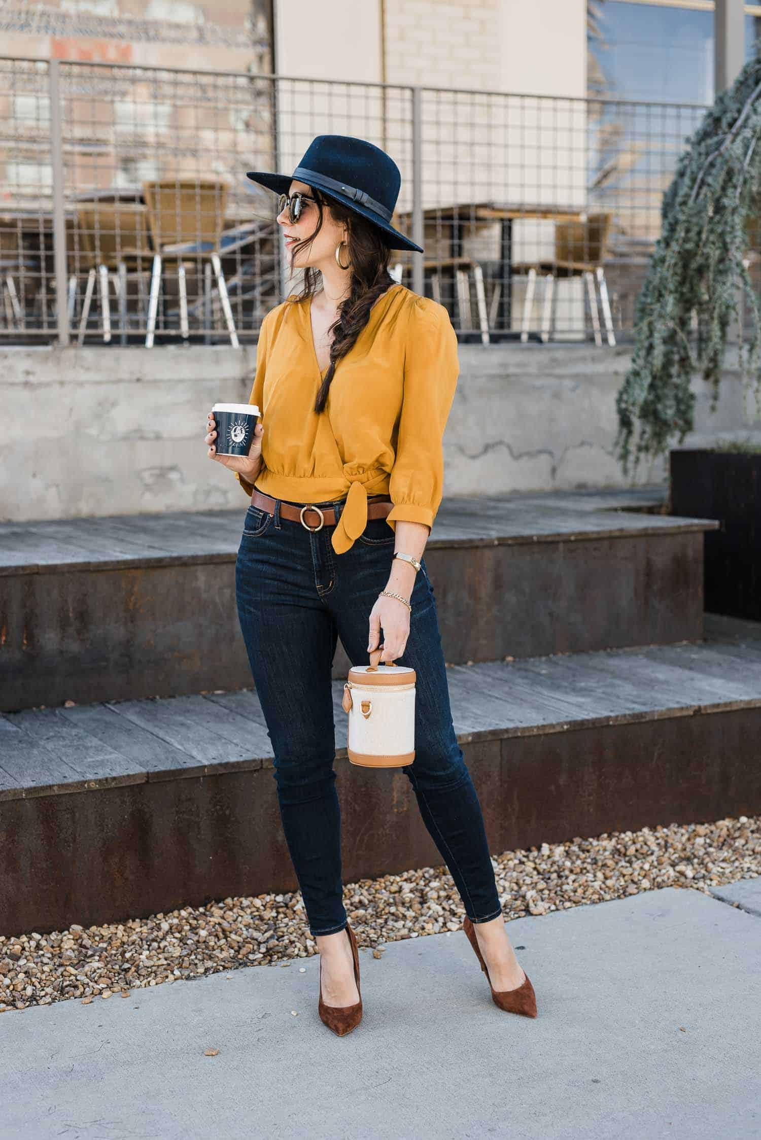 Jessica Camerata is wearing a mustard silk top, jeans and brown heels
