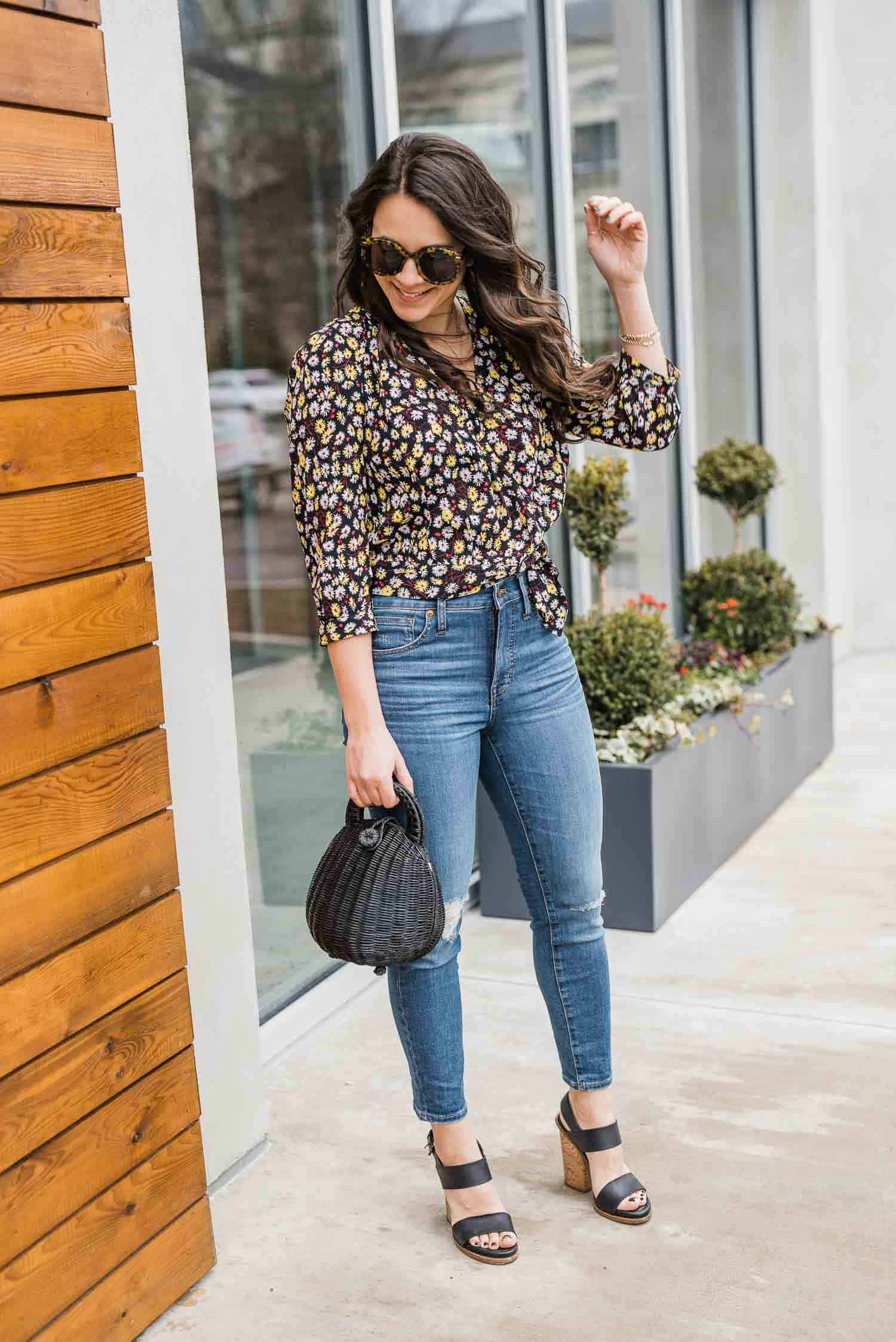 Jessica Camerata is wearing a Madewell wrap floral print blouse, Madewell jeans, Vince shoes, Karen Walker sunglasses and a Cult Gaia Millie bag.