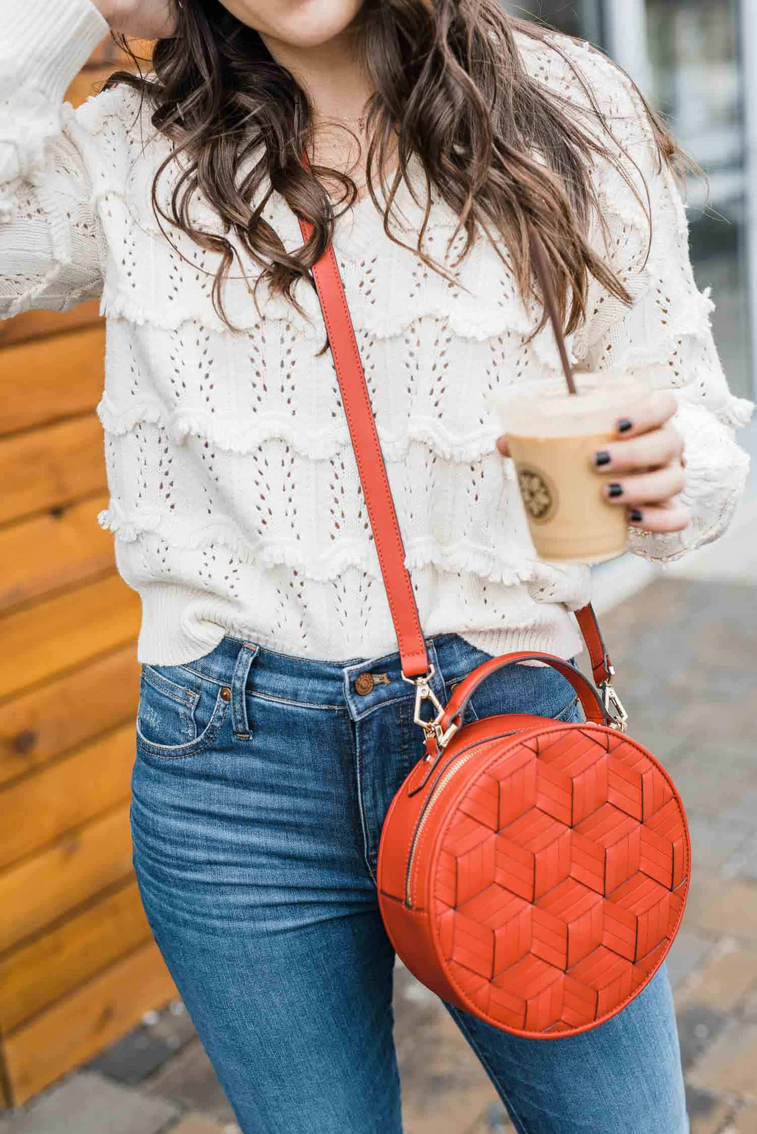 cream sweater details with fringe, red leather bag