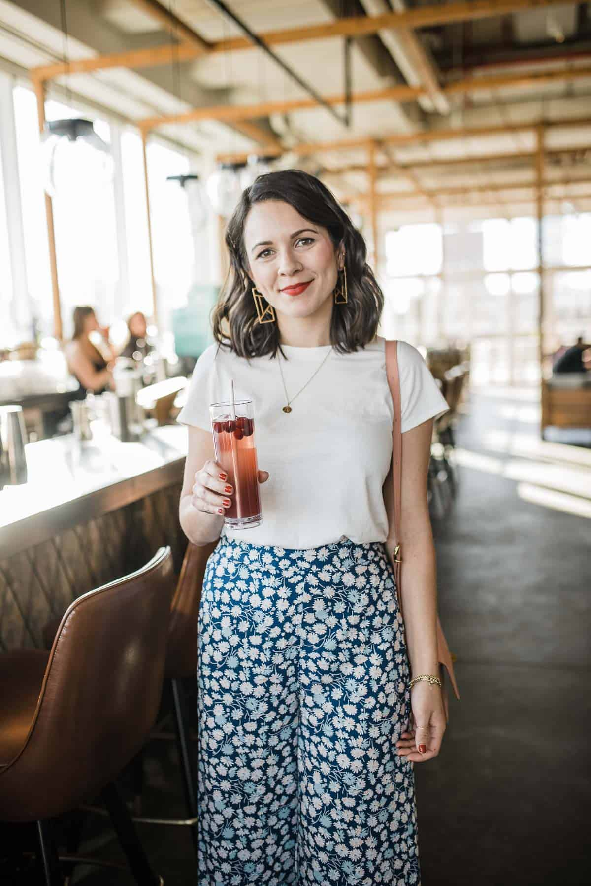 Jessica Camerata is wearing blue floral crop pants and white tee