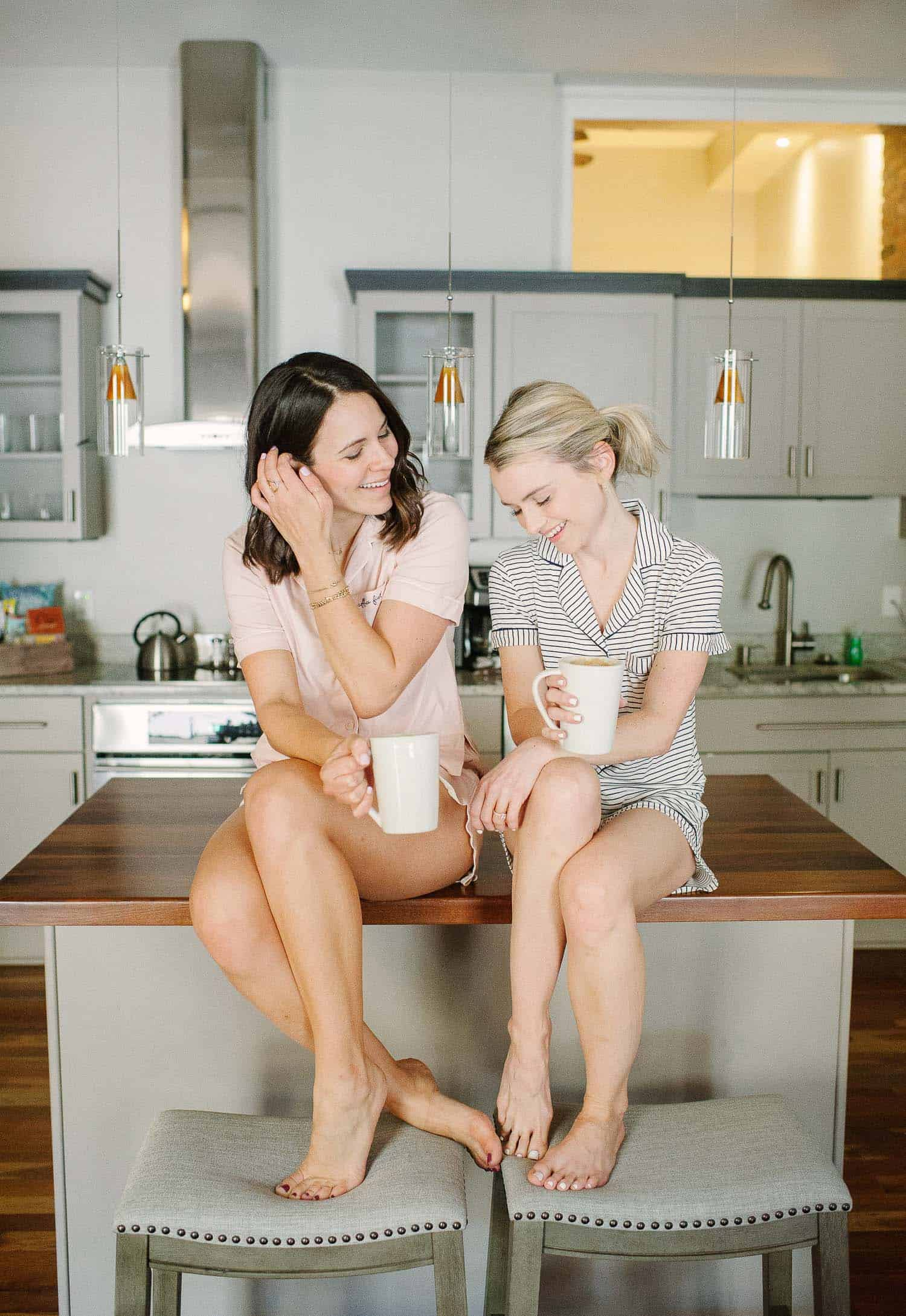 Girlfriends sitting on the counter together, friends traveling together, drinking coffee with friends