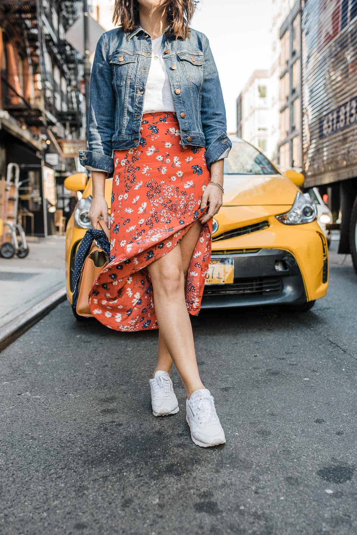 A denim jacket, white tee, floral skirt and white sneakers outfit.