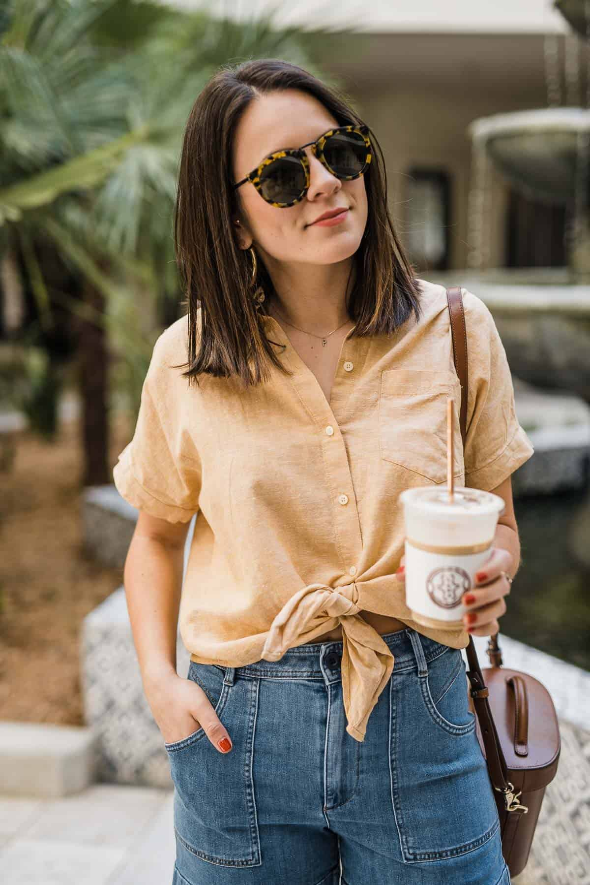 yellow button down with an iced coffee