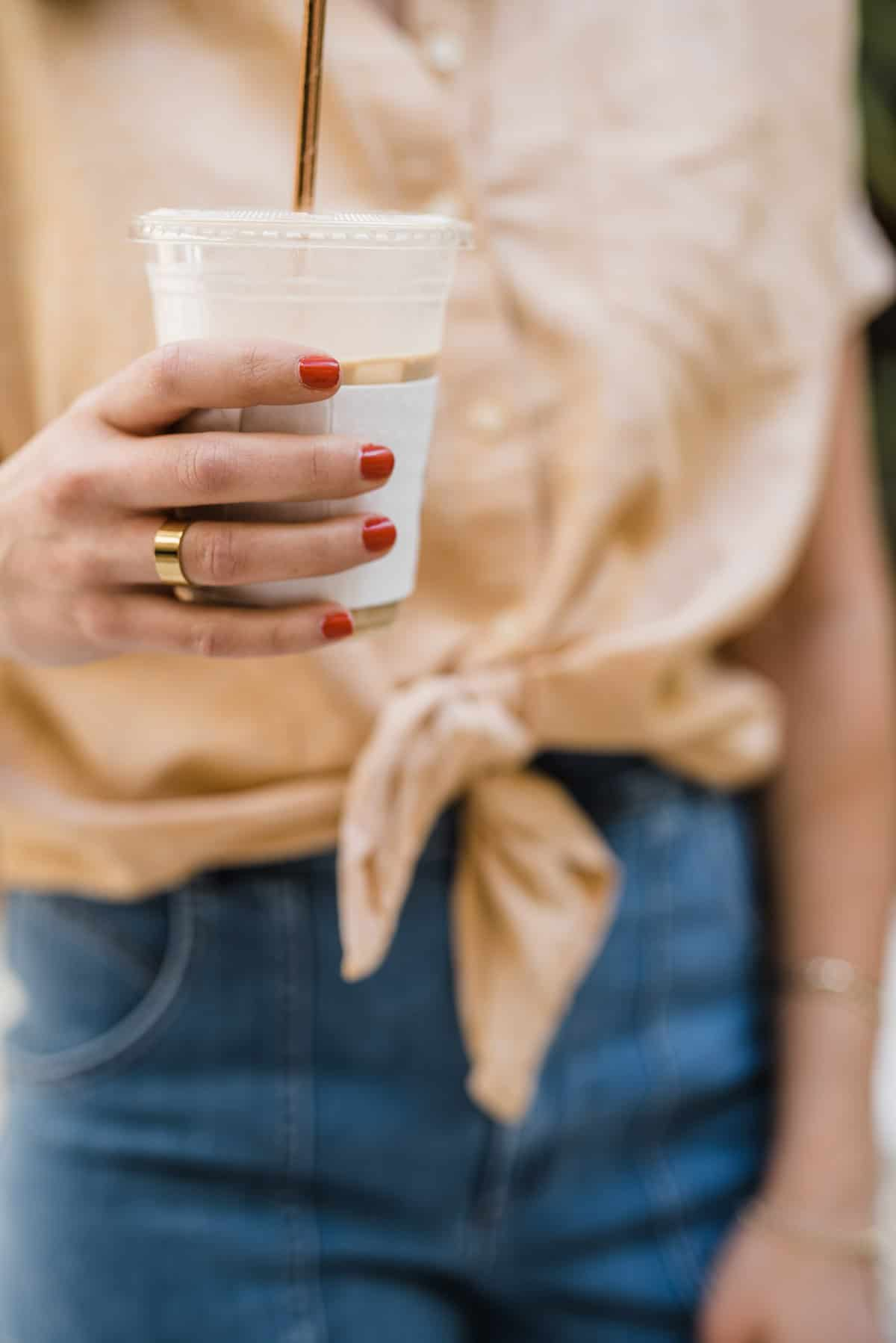 Jessica is holding an iced coffee, red nail polish and gold jewelry