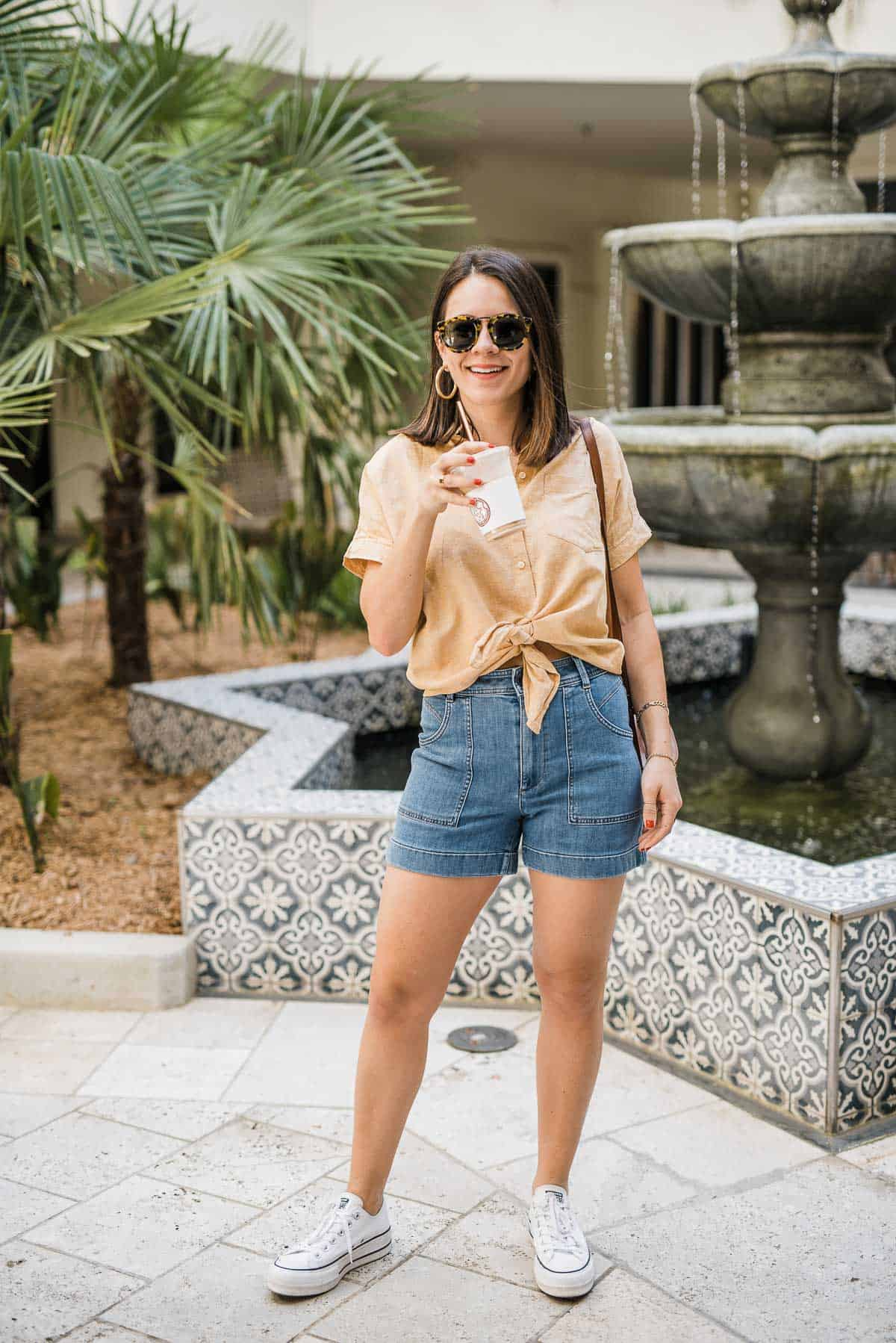 Jessica Camerata wears a Madewell button down and Madewell shorts with Converse