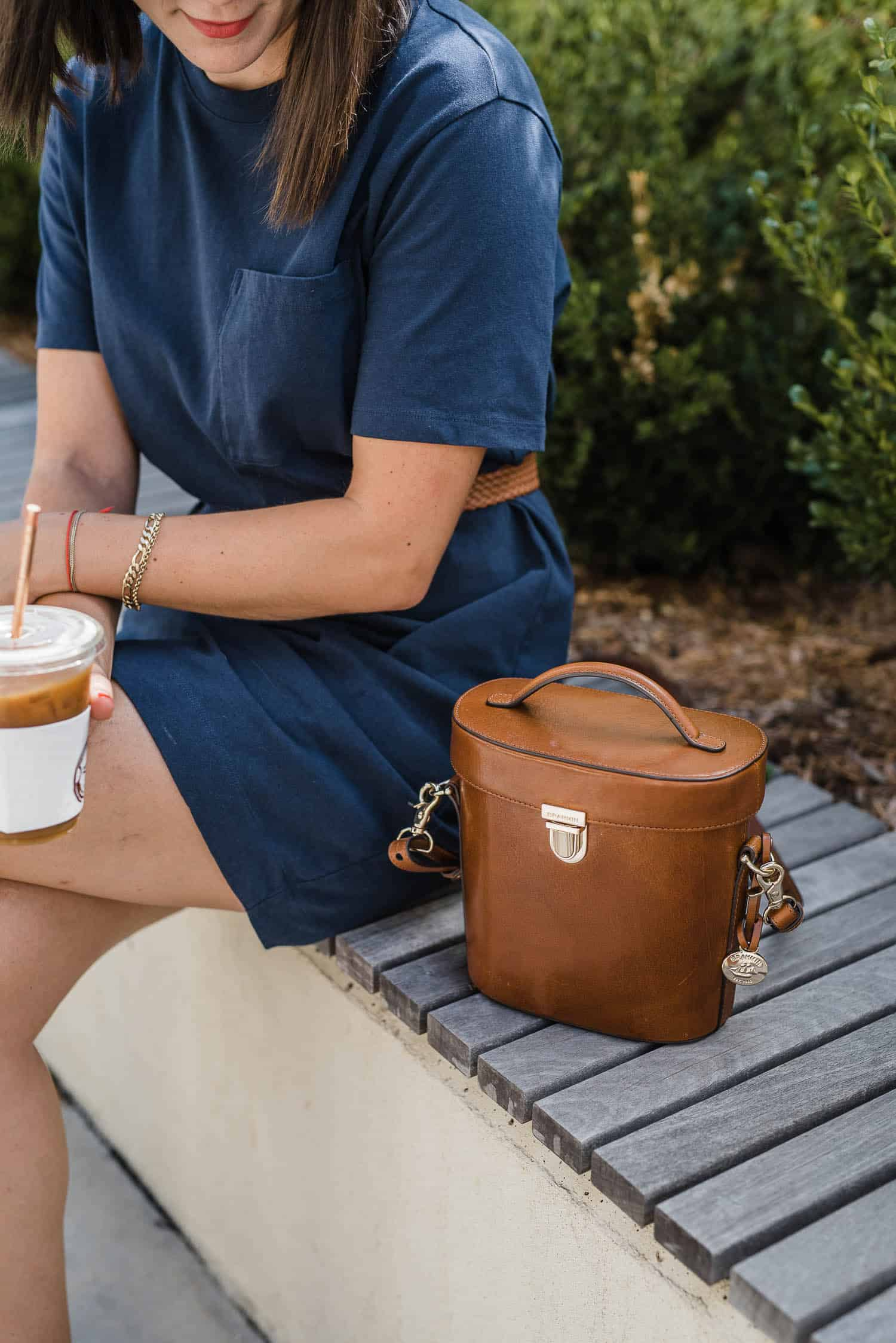 A structured bag pairs well with a belt and t-shirt dress