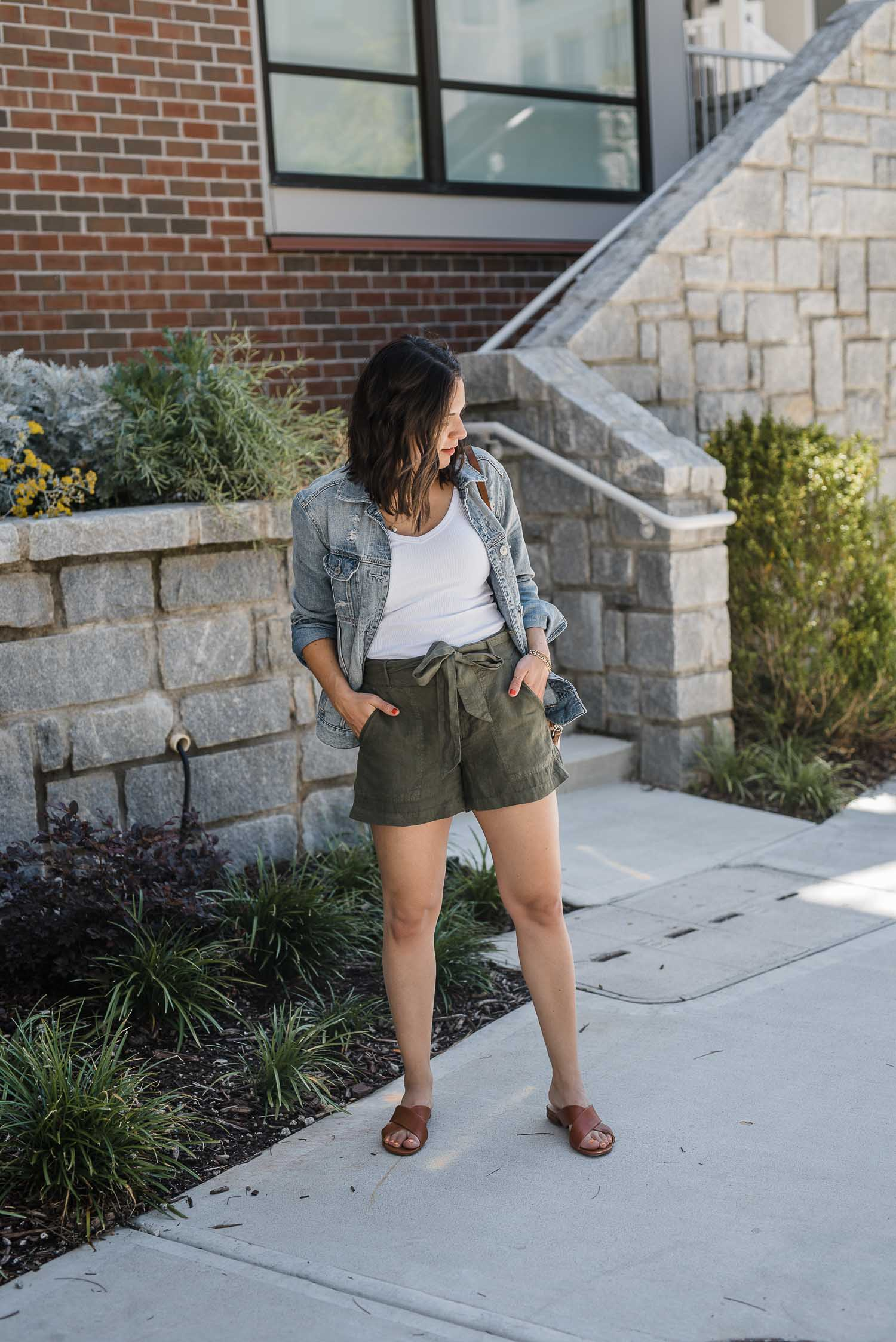 a girl in shorts and a jean jacket and a white tank top