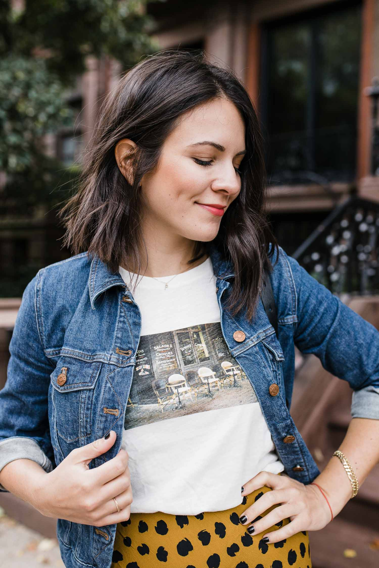 a graphic tee and a skirt and a jean jacket on a girl