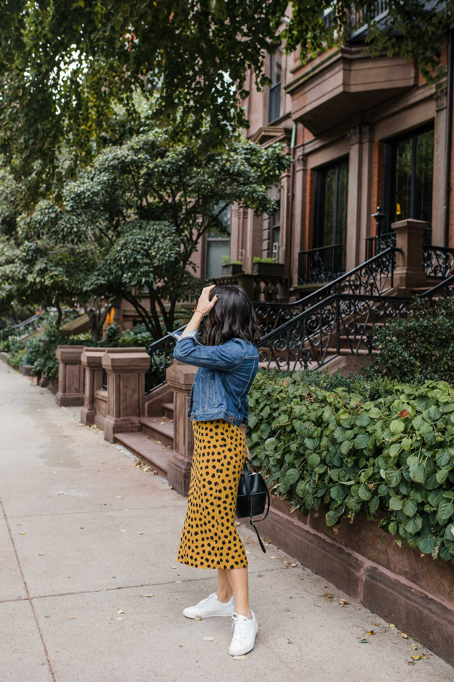a girl wearing a spotted skirt to transition into fall with