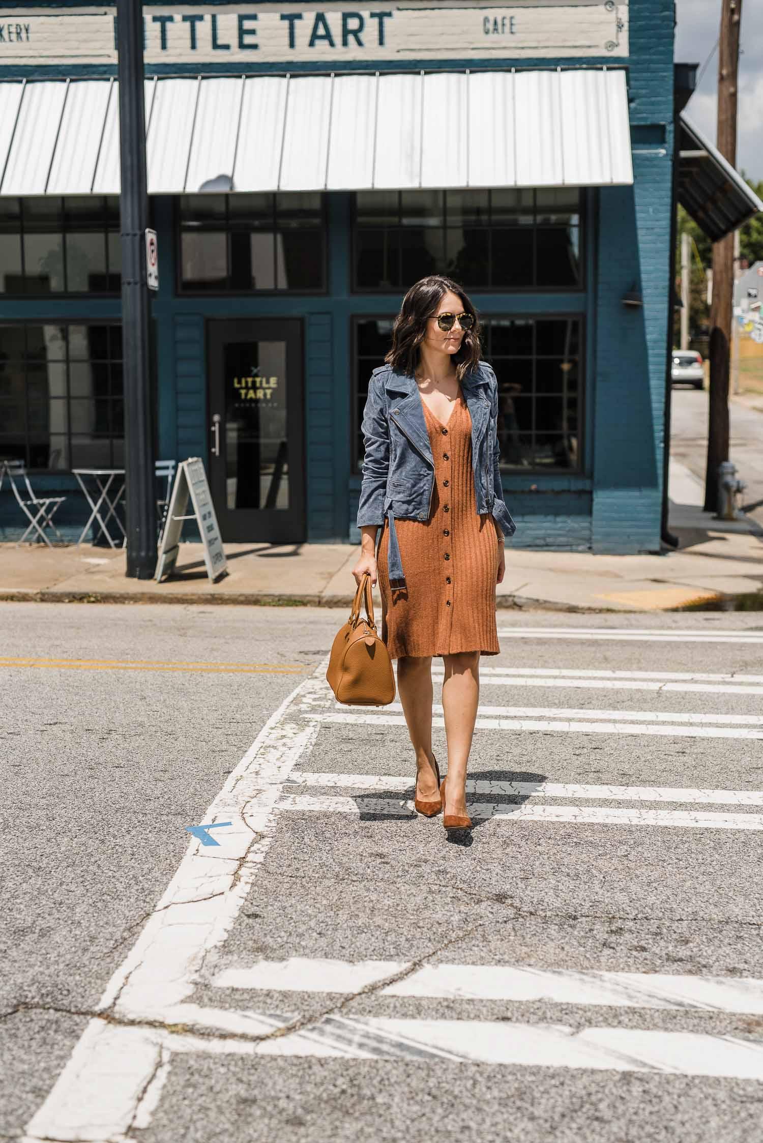 a girl walks across the street in a biege dress and heels