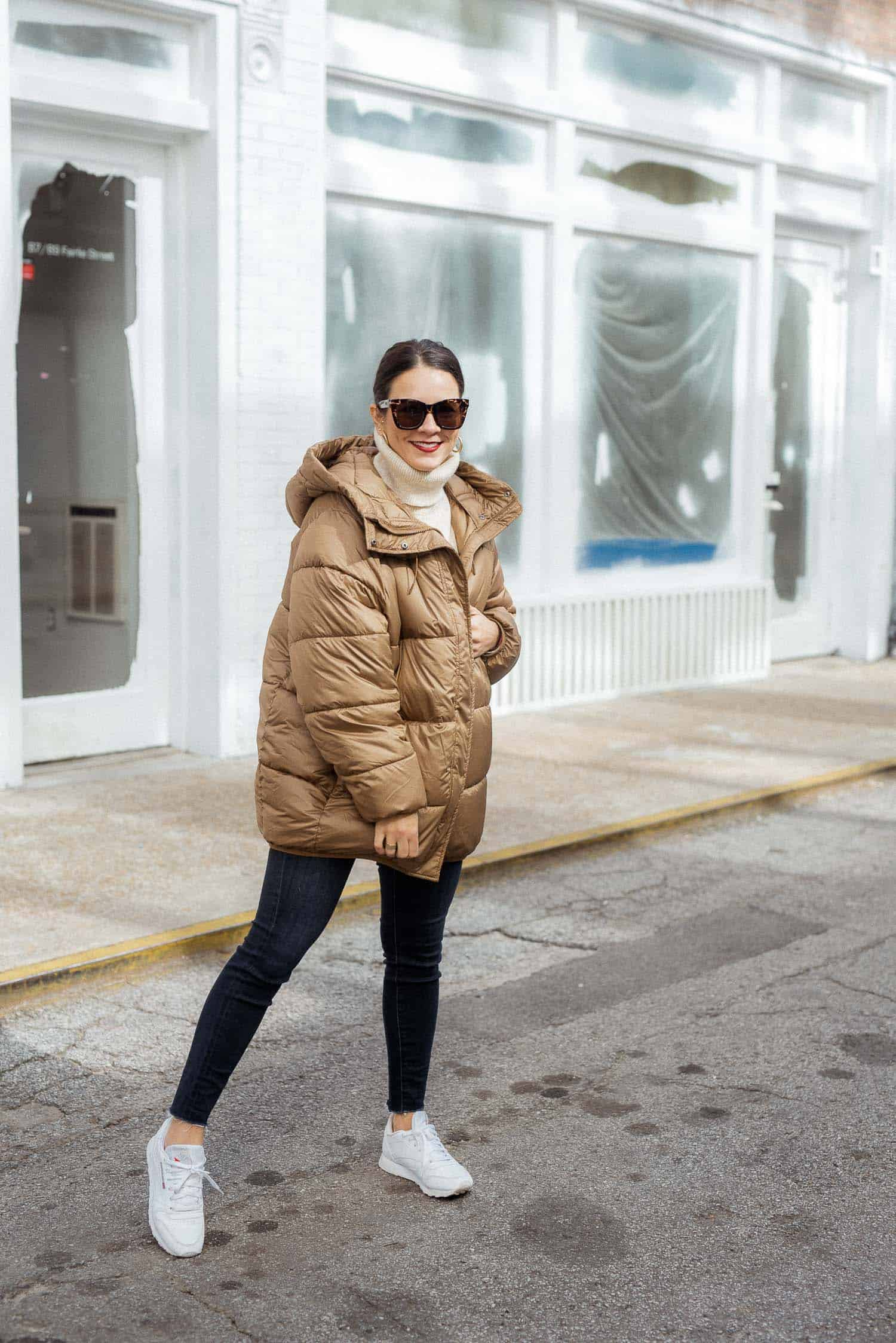 Jessica of My Style Vita wearing a stylish puffy coat and a pair of white Reeboks.
