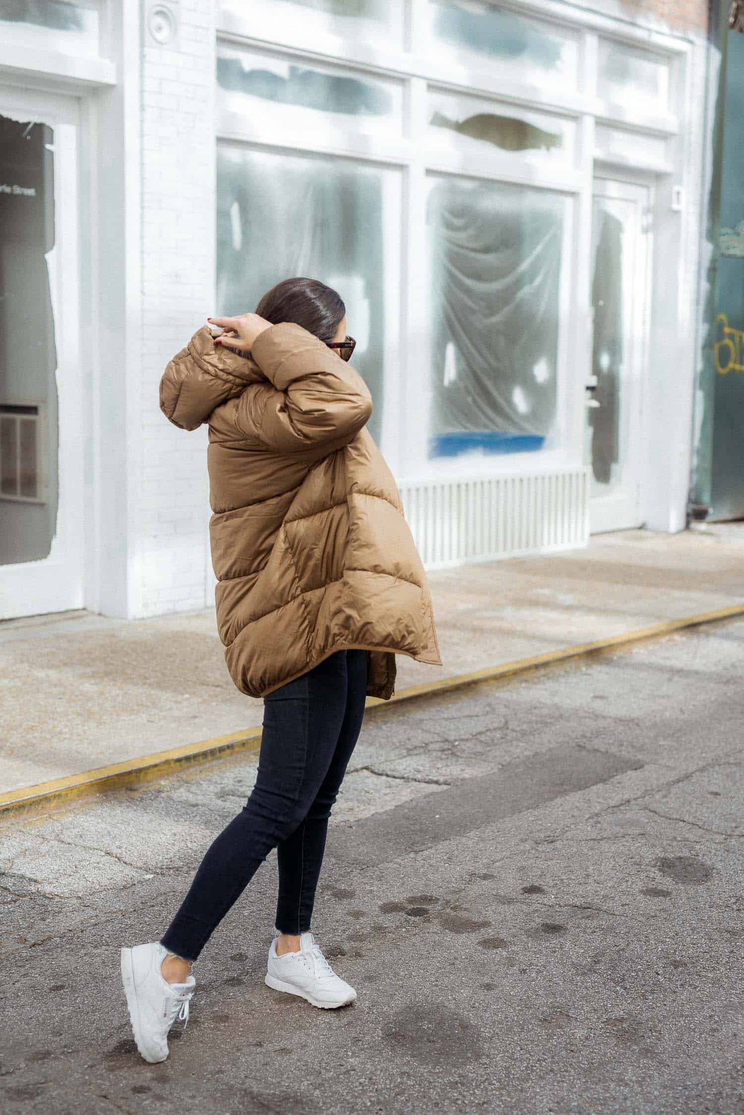 Jessica wearing a puffy coat, skinny jeans, and white Reeboks.
