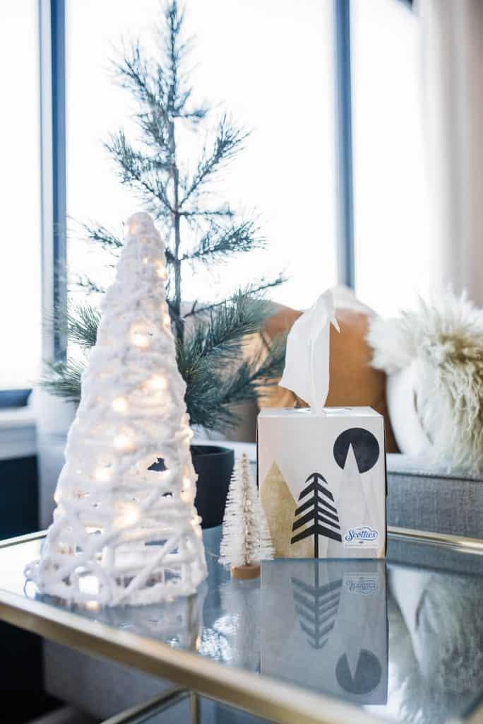 A pretty tissue box beside a white tabletop Christmas tree.