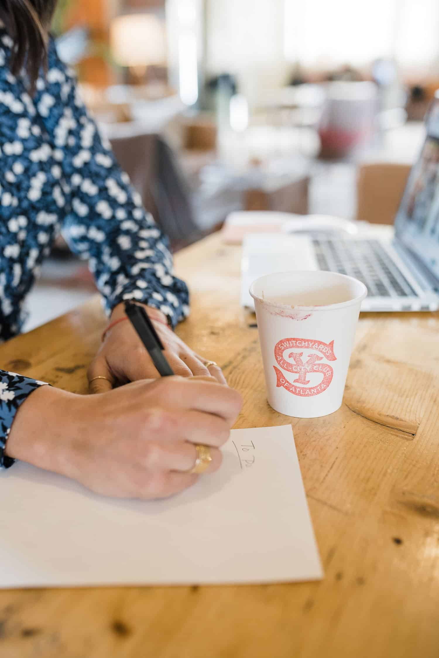 blogger writing down to do list with coffee